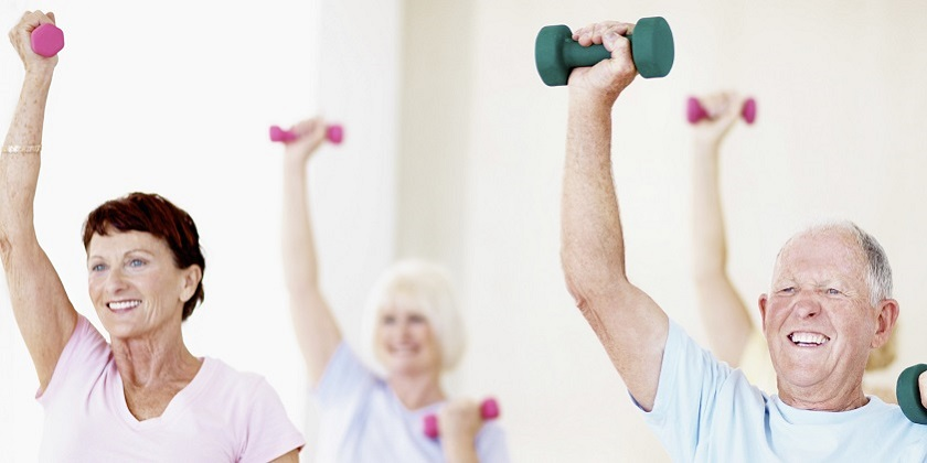 A group of smiling seniors lifting small dumbells in an exercise class
