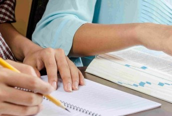 Hands writing notes with a pencil, with open text book alongside notebook
