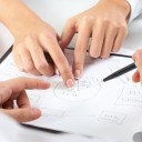Two pairs of hands pointing out parts of a plan in an office environment